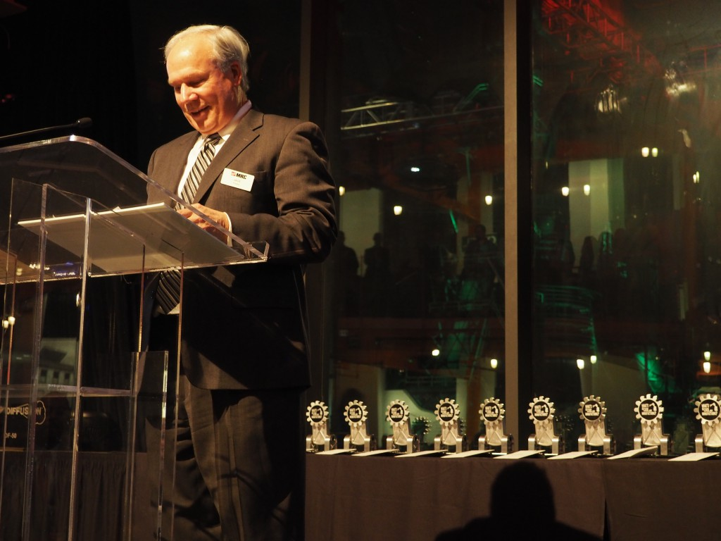 Jack Pfunder, President and CEO of MRC, speaking at the ArtsQuest Center in Bethlehem, with the trophies for the winning student videos behind him.