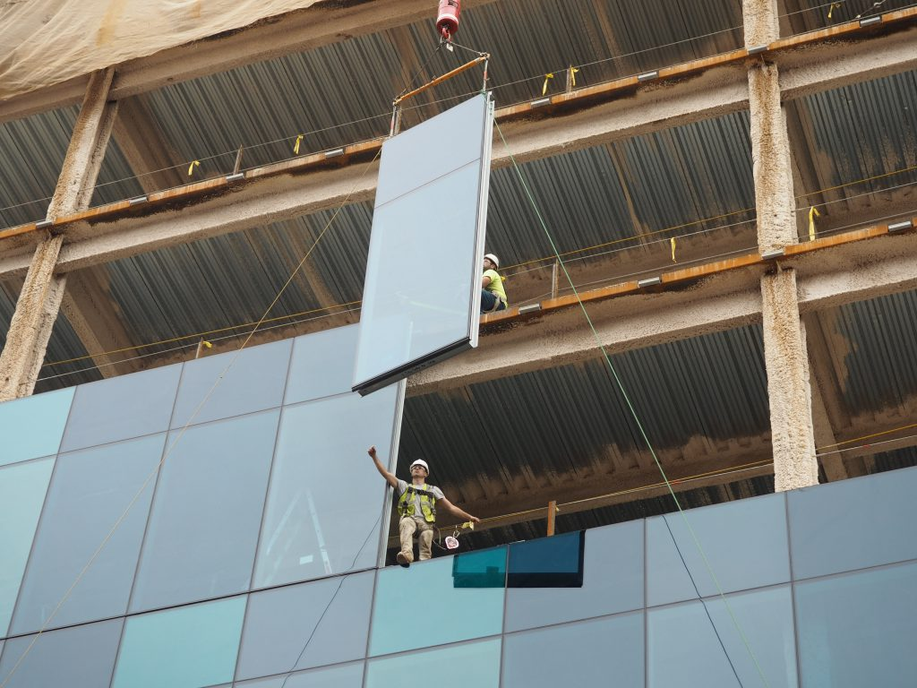 A construction worker installing one of the glass and steel panels at Five City Center in Allentown.